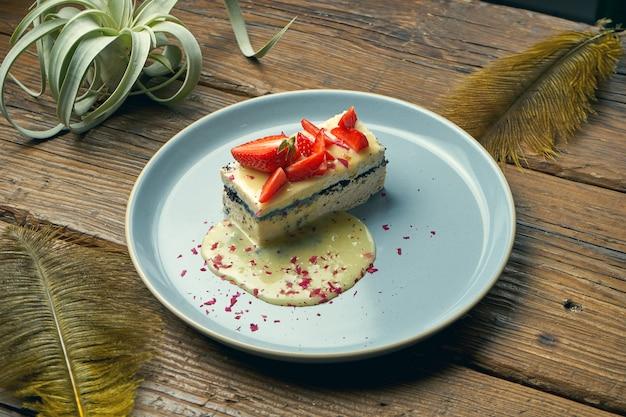 Zdrowy deser - zapiekanka z twarogu z makiem i truskawkami w talerzu na drewnianym stole
