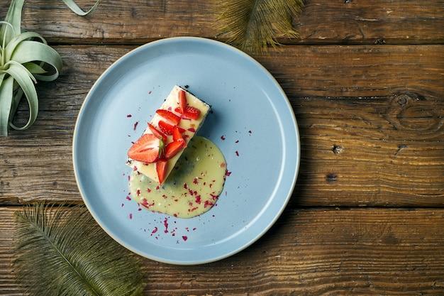 Zdrowy deser - zapiekanka z twarogu z makiem i truskawkami w talerzu na drewnianym