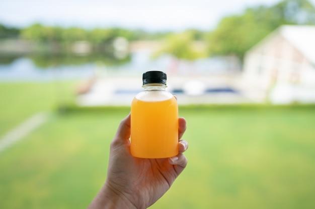 Zdrowy detoks z sokiem pomarańczowym. zbliżenie świeżej pomarańczowej butelce w ręku i zielonym tle przyrody.