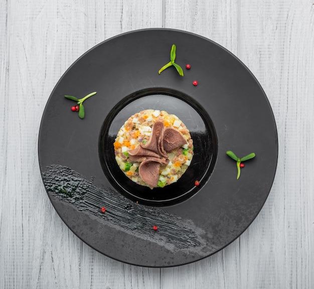 Zdrowy domowej roboty rosyjski tradycyjny sałatkowy olivier przygotowywający jeść w talerzu, zamyka up