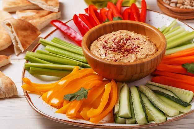 Zdrowy domowy hummus z bukietem świeżych warzyw i chlebem pita.