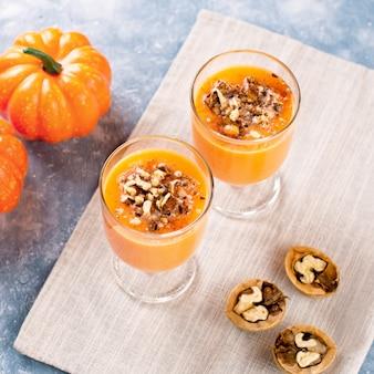Zdrowy dyniowy smoothie z orzechami włoskimi i cynamonem w szkłach na nieociosanym tle