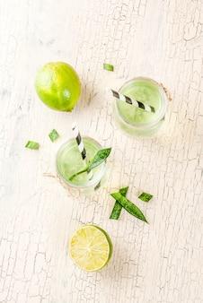 Zdrowy egzotyczny napój detox, aloes lub sok z kaktusa z limonką, na jasnym tle betonu