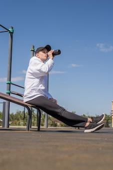 Zdrowy i aktywny tryb życia. sport i fitness. młoda sportive kobieta w sportowych ubraniach pije wodę z termosu na boisku sportowym