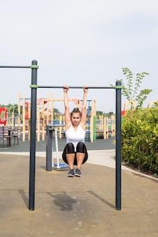 Zdrowy i aktywny tryb życia. sport i fitness. szczęśliwa kobieta w białej koszulce ćwiczącej na boisku sportowym w słoneczny letni dzień, ćwicząc mięśnie brzucha na barach