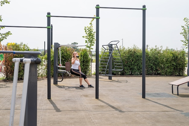 Zdrowy i aktywny tryb życia. sport i fitness. szczęśliwa kobieta w białej koszulce ćwiczącej na boisku sportowym w słoneczny letni dzień, pijąca wodę z termosu