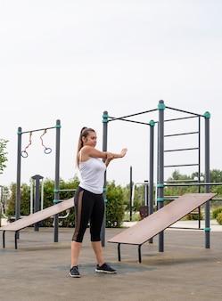Zdrowy i aktywny tryb życia. sport i fitness. szczęśliwa kobieta w białej koszulce ćwiczącej na boisku sportowym w słoneczny letni dzień, rozgrzewka