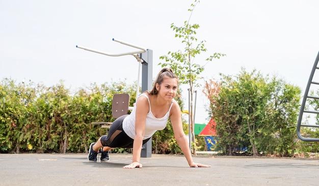 Zdrowy i aktywny tryb życia. sport i fitness. szczęśliwa kobieta w białej koszulce ćwiczącej na boisku sportowym w słoneczny letni dzień, stojąca na ziemi w pozycji deski, ćwicząc mięśnie brzucha