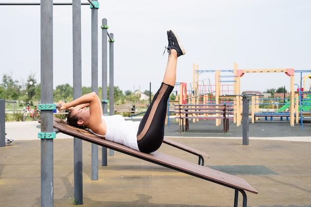 Zdrowy i aktywny tryb życia. sport i fitness. szczęśliwa kobieta w białej koszulce ćwiczącej na boisku sportowym w słoneczny letni dzień, trenująca abs