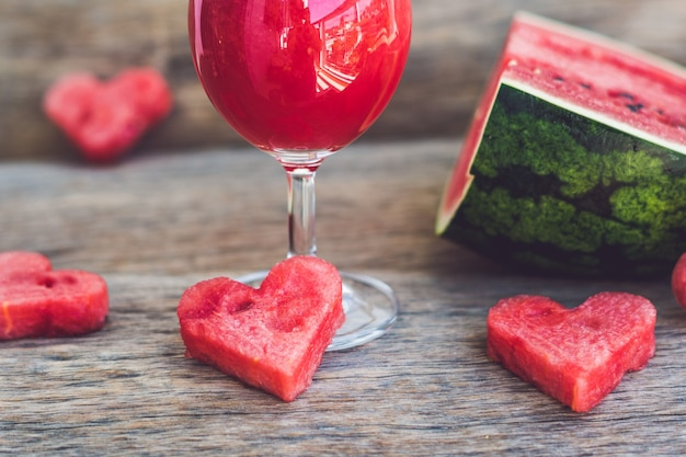 Zdrowy koktajl arbuzowy, kawałek arbuza, serca i pasiasta słomka na drewnianym stole