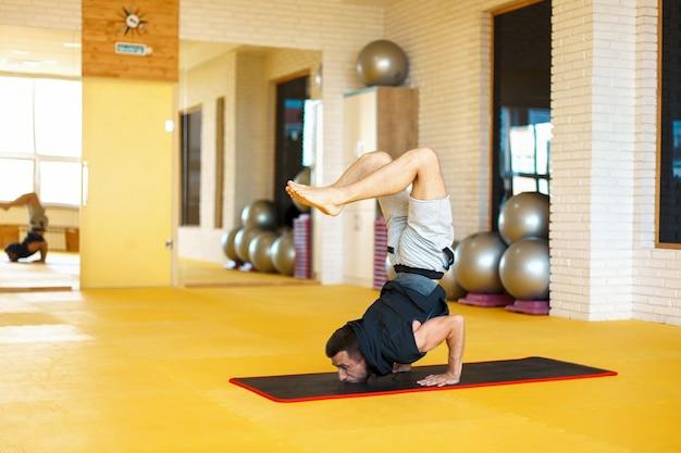 Zdrowy mężczyzna ćwiczy jogę i pozę skorpiona na siłowni.