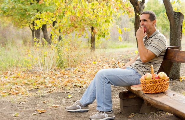 Zdrowy mężczyzna w średnim wieku siedzi samotnie na rustykalnej drewnianej ławce w lesie z koszem świeżo zerwanych jabłek, jedząc jabłko