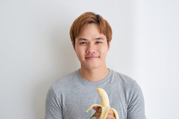 Zdrowy młody azjatycki człowiek je banana w domu.