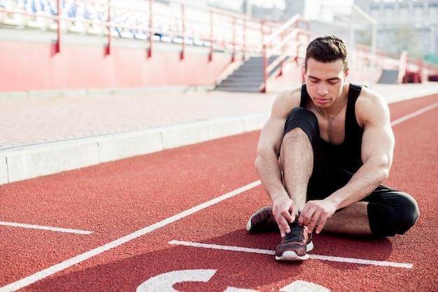 Zdrowy młody człowiek siedzi na bieżni wiążąc jego sznurowadło