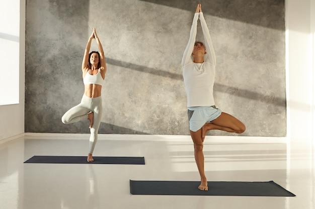 Zdrowy, muskularny młody kaukaski mężczyzna w krótkich spodenkach i dopasowana szczupła kobieta w leginsach stojąca boso na matach w przestronnej siłowni podczas porannych zajęć jogi, wykonując pozę vrksasana lub ćwiczenia asany drzewa