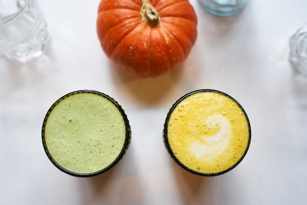 Zdrowy napój kurkuma i imbirowa żółta latte z mlekiem kokosowym i wegańską matchą
