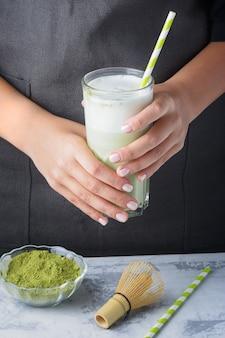 Zdrowy napój matcha. barista trzyma w dłoniach szklankę latte z zieloną herbatą.