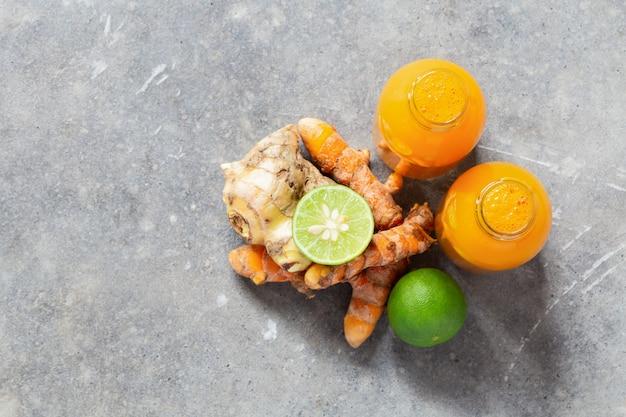Zdrowy napój z korzenia kurkumy i imbiru oraz wapna w małych butelkach na szarej betonowej ścianie z copyspace.