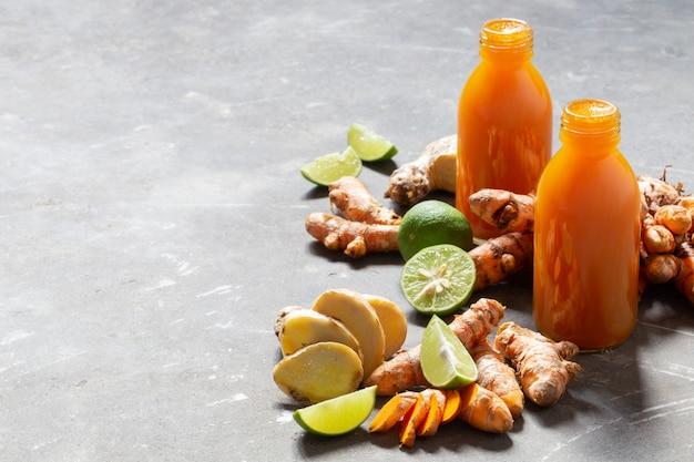 Zdrowy napój z kurkumy, korzenia imbiru i wapna w małych butelkach na szarej betonowej ścianie.