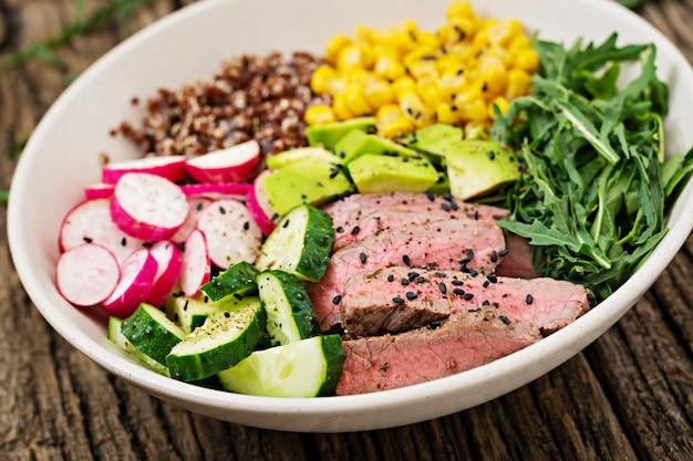 Zdrowy obiad lunch w misce buddy z grillowanym stekiem wołowym i komosą ryżową, kukurydzą, awokado, ogórkiem i rukolą na drewnianym stole. sałatka mięsna