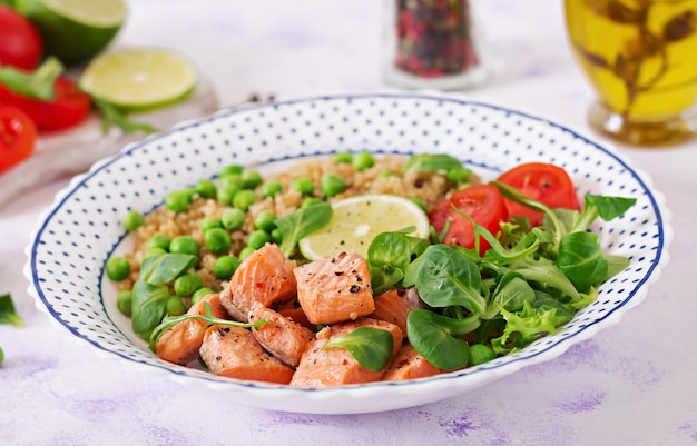 Zdrowy obiad plastry grillowanego łososia, komosy ryżowej, zielonego groszku, pomidorów, limonki i liści sałaty