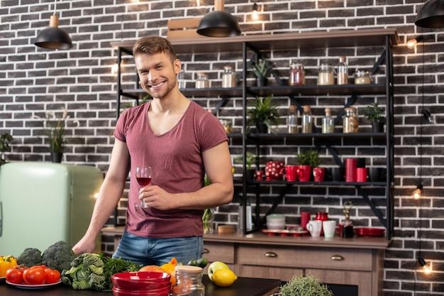 Zdrowy obiad. przystojny blondyn w dżinsach i koszulce gotuje zdrowy obiad dla uroczej żony