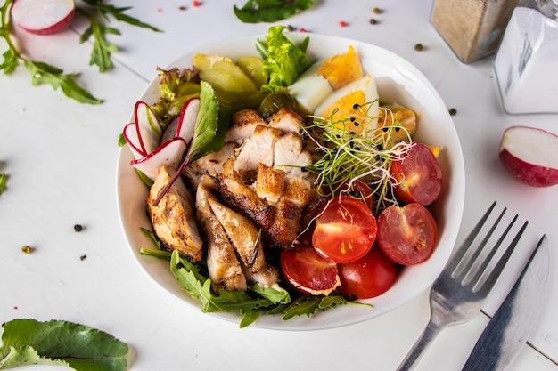 Zdrowy obiad w misce buddy z pieczonym kurczakiem, komosą ryżową, pomidorami koktajlowymi, rzodkiewką, jajkami, ogórkiem kiszonym, mikrogreenami i rukolą