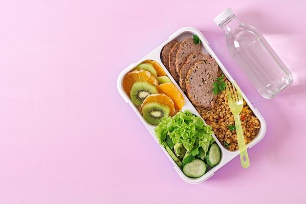 Zdrowy obiad z bulgur, mięsem i świeżymi warzywami i owocami na różowej powierzchni. koncepcja fitness i zdrowego stylu życia. pudełko śniadaniowe. widok z góry