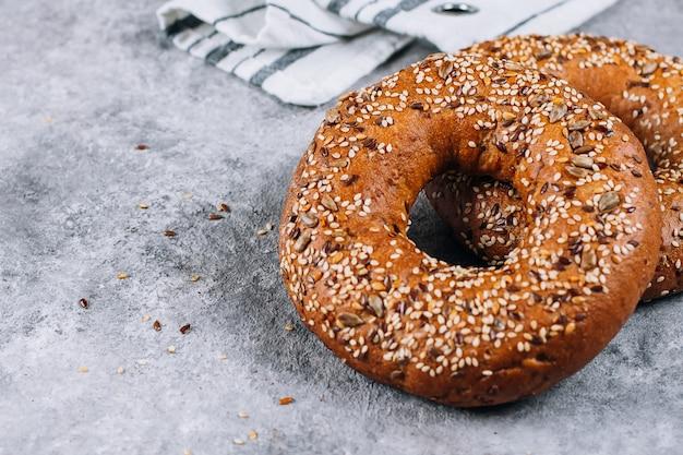 Zdrowy organicznie cały zbożowy bagel na betonowym tło stole