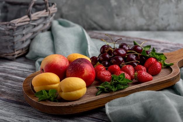 Zdrowy owocowy półmisek, truskawki, jabłka, brzoskwinie, morele na zmroku - szary drewniany stół, odgórny widok, zakończenie, selekcyjna ostrość.
