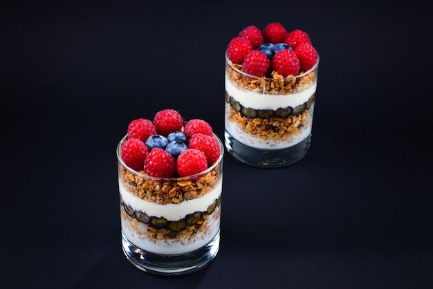 Zdrowy parfait jagodowy i malinowy w szklance na czarnym tle. dwie porcje. miejsce na tekst lub projekt.