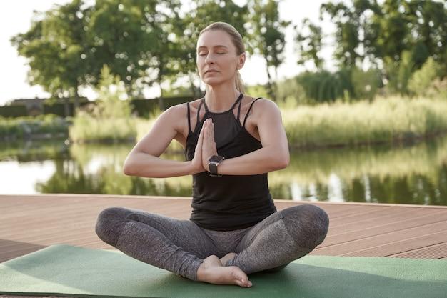 Zdrowy poranek młoda piękna kobieta w stroju sportowym, trzymając zamknięte oczy, siedząc w pozycji lotosu na