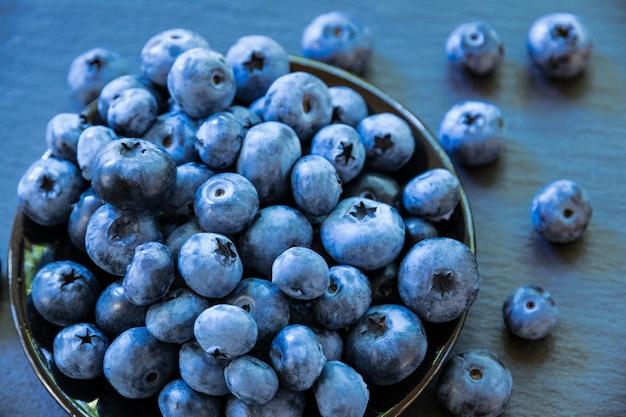 Zdrowy produkt jagody jagodowe są na ciemnym kamiennym blacie rozsypane letnie jagody na stole
