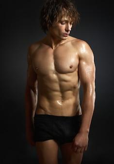 Zdrowy przystojny mięśniowy młody człowiek w studiu