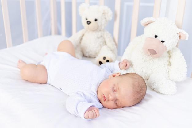 Zdrowy sen noworodka w łóżeczku w sypialni z pluszowym misiem na bawełnianym łóżeczku