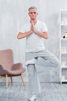 Zdrowy starszy mężczyzna ćwiczy joga patrzeje kamerę