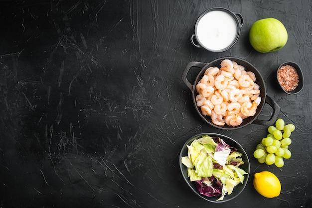 Zdrowy styl życia - gotowanie świeżej sałatki z krewetek, zielonej sałaty, zestawu oliwek, z sosem jabłkowym i winogronowym, na czarnym tle kamienia, widok z góry na płasko, z miejscem na tekst