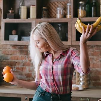 Zdrowy styl życia. korzyści z żywności ekologicznej. bilans składników odżywczych. młoda blond kobieta taniec z owocami.