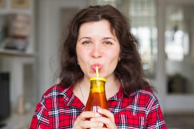Zdrowy styl życia, napoje witaminowe i koncepcja diety - bliska szczęśliwa kobieta pije sok w domu