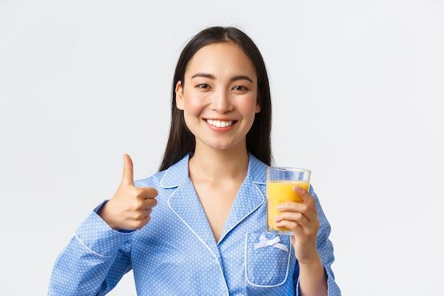 Zdrowy styl życia, poranna rutyna i koncepcja ludzi. zbliżenie optymistycznej uśmiechniętej azjatyckiej kobiety w niebieskiej piżamie pokazującej kciuk w górę i pijącej sok na produktywny dzień, pełen witamin.