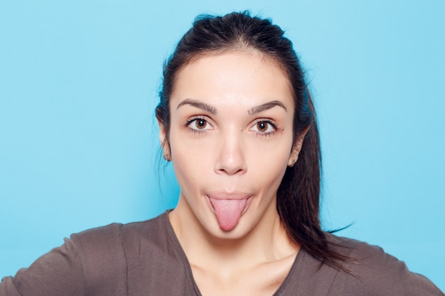 Zdrowy styl życia, szczęście i koncepcja ludzie - piękna uśmiechnięta kobieta na niebieskim tle. emocjonalna dziewczyna. piękny nowożytny model pokazuje język pozytywnej kobiety modniś. emocje na twarzy.