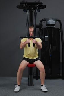 Zdrowy styl życia - zwykły młody człowiek uprawiający sport na siłowni