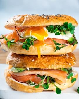 Zdrowy, świeżo upieczony bajgiel wypełniony łososiem, microgreenem, awokado i jajkiem. serwowane na białym biurku. kanapka z łososiem. zdrowe śniadanie.