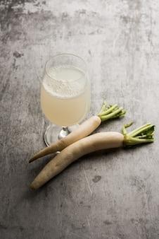 Zdrowy świeży sok daikon lub napój z ekstraktu mooli w szklance z surowym mułem