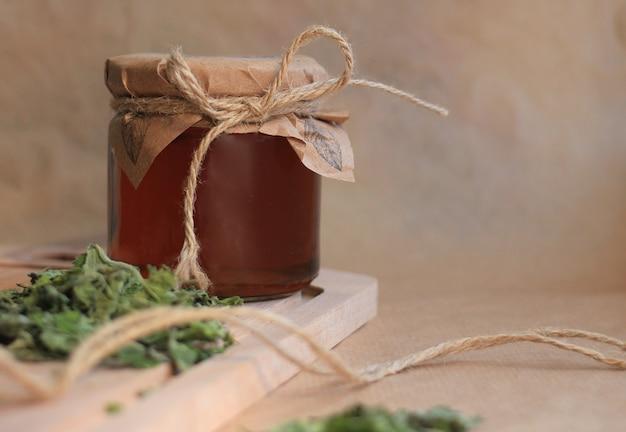 Zdrowy syrop miętowy w szklanym słoju na beżowym tle z suchymi listkami mięty