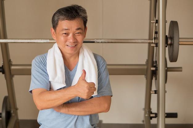 Zdrowy, szczęśliwy starszy mężczyzna ćwiczy w siłowni, podając kciuk gest