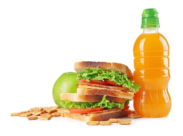 Zdrowy szkolny lunch z kanapką, owocami i sokiem na białym tle
