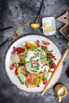 Zdrowy talerz sałatkowy. przepis na świeże owoce morza. łosoś wędzony, sałata, suszone pomidory i sos serowy. zdrowe jedzenie. leżał płasko. widok z góry,