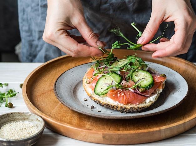Zdrowy tost z twarogiem, łososiem, świeżym ogórkiem, kaparami, czerwoną cebulą, czarnym pieprzem i niepewną kobietą leży na kiełkach groszku.
