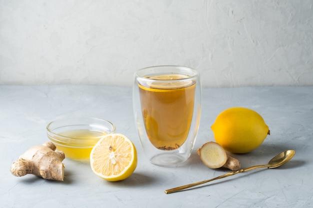 Zdrowy tryb życia herbata ziołowa cytrynowo-miodowa z korzeniem imbiru na szarej powierzchni
